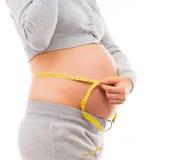 Vientre de una mujer embarazada joven con una cinta métrica Imágenes de archivo libres de regalías