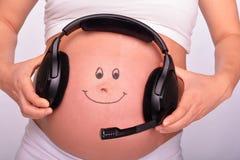 Vientre del bebé con auriculares Fotografía de archivo libre de regalías