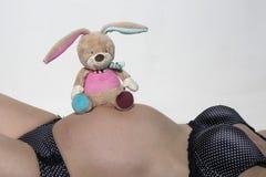 Vientre del bebé con el pequeño juguete de la felpa Foto de archivo libre de regalías