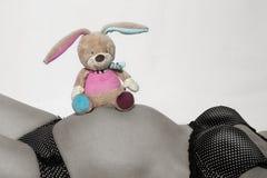 Vientre del bebé con el pequeño juguete de la felpa Imagenes de archivo
