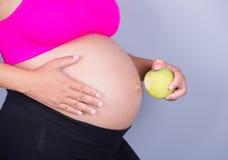 Vientre del primer de la mujer embarazada con la manzana verde en backgr gris Imágenes de archivo libres de regalías