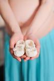 Vientre embarazada con botines recién nacidos del bebé Imagen de archivo