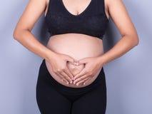 Vientre embarazada con forma del corazón de los fingeres Imagenes de archivo