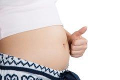 Vientre embarazada con símbolo de los fingeres Foto de archivo