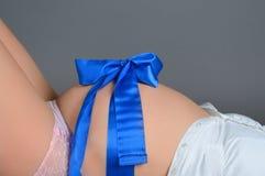 Vientre embarazada con una cinta Imagen de archivo libre de regalías