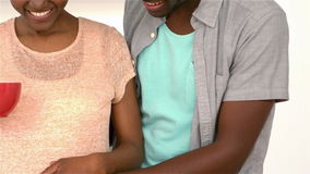 Vientre embarazada conmovedor de los pares felices que sostiene las tazas almacen de metraje de vídeo