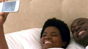 Vientre embarazada conmovedor de los pares felices que toma el selfie almacen de metraje de vídeo
