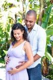 Vientre embarazada conmovedor sonriente de la esposa del marido Imagenes de archivo