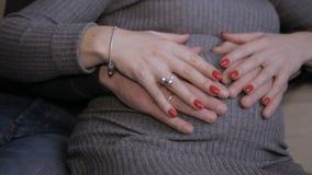 Vientre embarazada de la caricia masculina y femenina de las manos almacen de metraje de vídeo