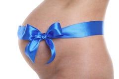 Vientre embarazado con la cinta azul Foto de archivo libre de regalías