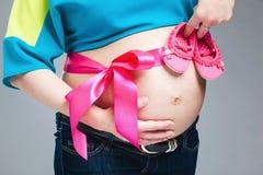 Vientre embarazado con la cinta rosada Imagen de archivo