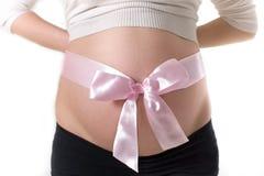 Vientre embarazado con la cinta rosada Fotografía de archivo