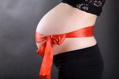 Vientre embarazado con un arqueamiento Fotografía de archivo