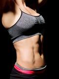 Vientre femenino muscular sobre negro Foto de archivo