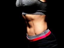 Vientre femenino muscular sobre negro Fotos de archivo