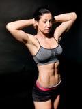 Vientre femenino muscular sobre negro Foto de archivo libre de regalías