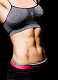 Vientre femenino muscular sobre negro Imagen de archivo
