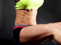 Vientre femenino muscular sobre negro Imagen de archivo libre de regalías