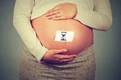 Vientre grande de la mujer embarazada con la muestra del reloj de la arena Imágenes de archivo libres de regalías
