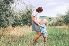 Vientre que se besa del muchacho del niño de embarazada su madre en backgro de la naturaleza Imagenes de archivo