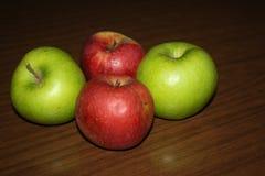 Vier Äpfel auf dem Holztisch Stockfotos