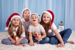 Vier aanbiddelijke jonge geitjes, peuterkinderen, die pret hebben voor Kerstmis Stock Foto