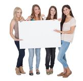 Vier aantrekkelijke meisjes die een witte raad houden Stock Afbeelding