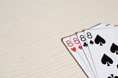 vier acht Pokerhandspielkarten auf einem hellen Schreibtischhintergrund Stockbild