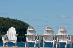 Vier Adirondack Stühle durch den See Stockbild