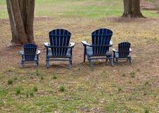 Vier adirondack Stühle im Wald Lizenzfreies Stockfoto