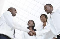 Vier afrikanische Teilhaber rütteln Hände Stockfoto