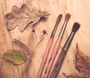 Vier alte benutzte Malerpinsel und Herbstlaub Stockfoto
