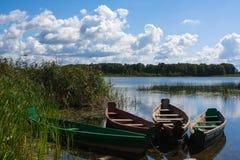 Vier alte hölzerne Boote auf dem Seeufer Stockbilder