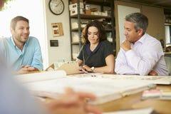 Vier Architecten die Lijst rondhangen die Vergadering hebben stock foto