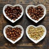 Vier Arten Kaffeebohnen im Herzen formten Schüsseln stockfoto