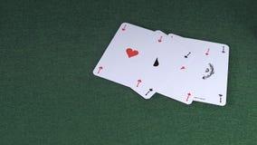 Vier As-Spielkarten, die gegen grünen Hintergrund fallen stock video