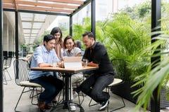 Vier asiatische junge lächelnde Freunde beim lustiges O zusammen aufpassen stockfoto