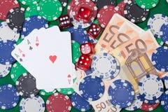 Vier Asse, Geld, Pokerchips und würfelt Lizenzfreie Stockfotos