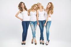 Vier attraktive Freundinnen in der Umarmung Stockbilder
