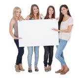 Vier attraktive Mädchen, die einen weißen Vorstand anhalten Stockbild