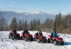 Vier ATV-ruiters op off-road vierlingfietsen in de winter Stock Fotografie