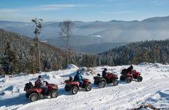 Vier ATV-ruiters op off-road vierlingfietsen op sneeuw in de winter Royalty-vrije Stock Afbeeldingen