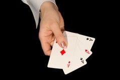 Vier azen in vrouwelijke hand op zwarte Stock Foto
