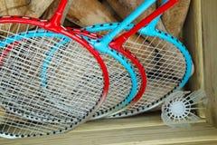 Vier badmintonrackets in een doos met croquethouten hamers en een shuttle stock foto's