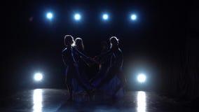 Vier ballerina's het dansen modern ballet in duisternis over schijnwerpers Langzame Motie stock footage