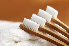 Vier bamboetandenborstels op witte handdoek stock foto