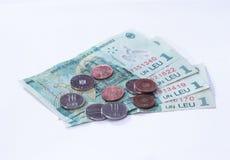 Vier Banknoten wert 1 Leu mit einigen Münzen wert 10 und 5 Rumänen Bani auf einem weißen Hintergrund Lizenzfreie Stockfotografie