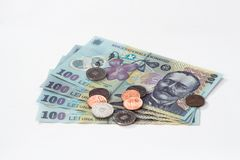 Vier Banknoten wert 100 rumänische Leu mit einigen Münzen wert 10 und 5 Rumänen Bani lokalisiert auf einem weißen Hintergrund Lizenzfreie Stockfotografie
