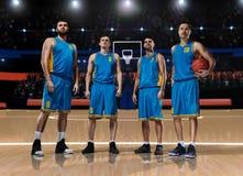 Vier Basketball-Spieler, die auf Basketballplatz stehen stockbilder