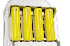 Vier batterijen in de lader Stock Afbeelding